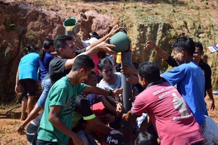 "Para peserta sedang berjuang mengisi air ke dalam pipa pada permainan ""pipa bocor"""
